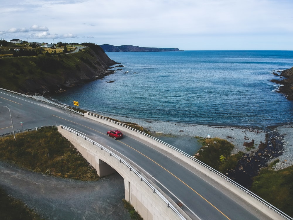 aerial photography of road with red vehicle traveling on road