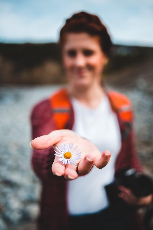 woman holds white petaled flower