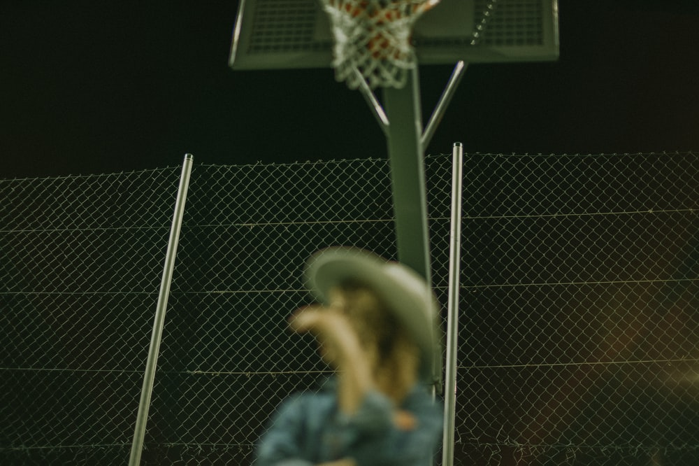 selective focus photography of woman wearing gray hat on basketball court