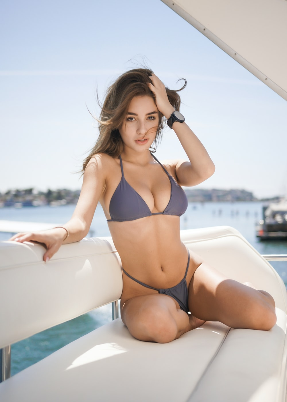 woman wears purple halter string bikini and sits on motorized boat