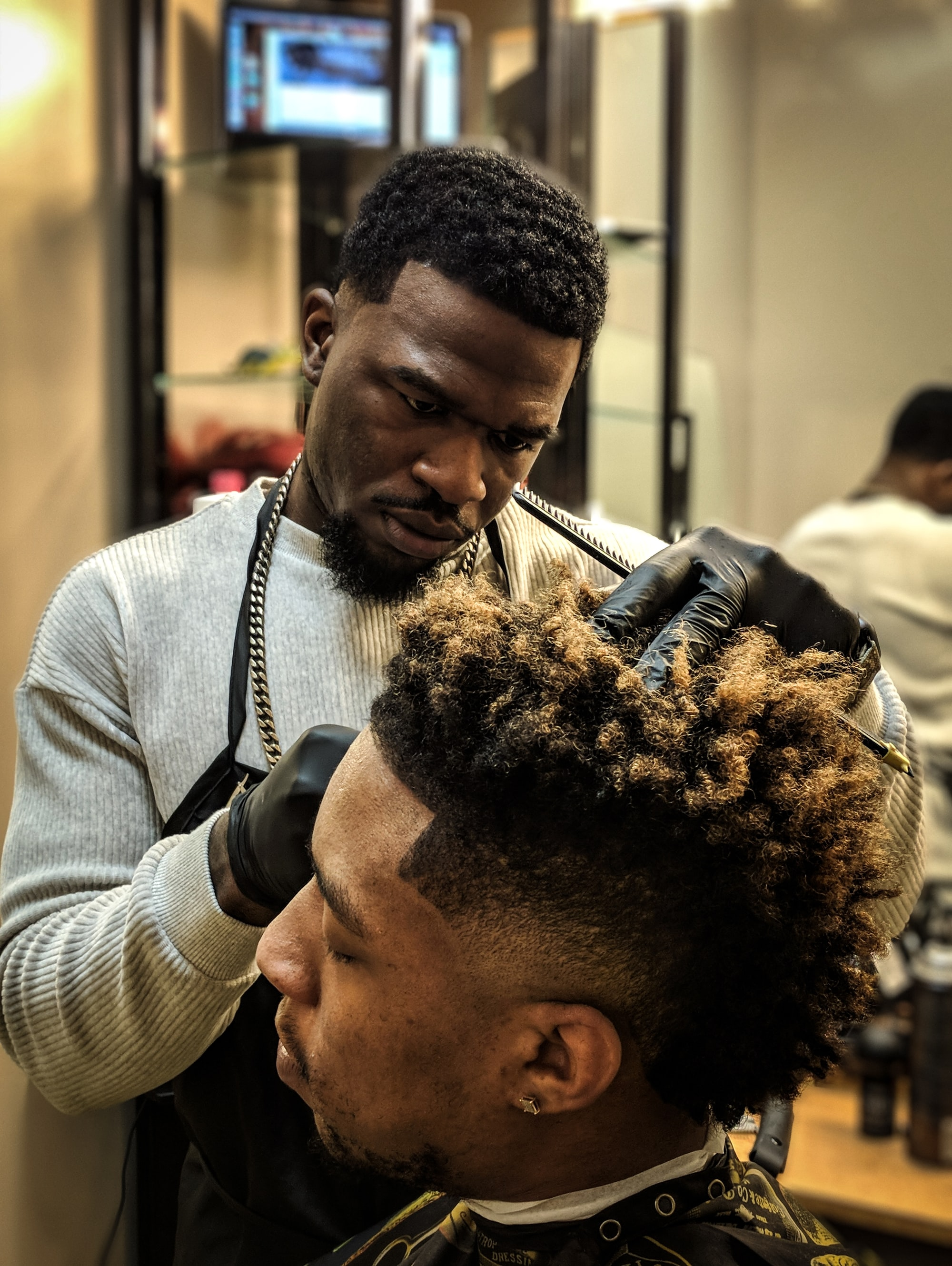 A barber working on his latest subject.