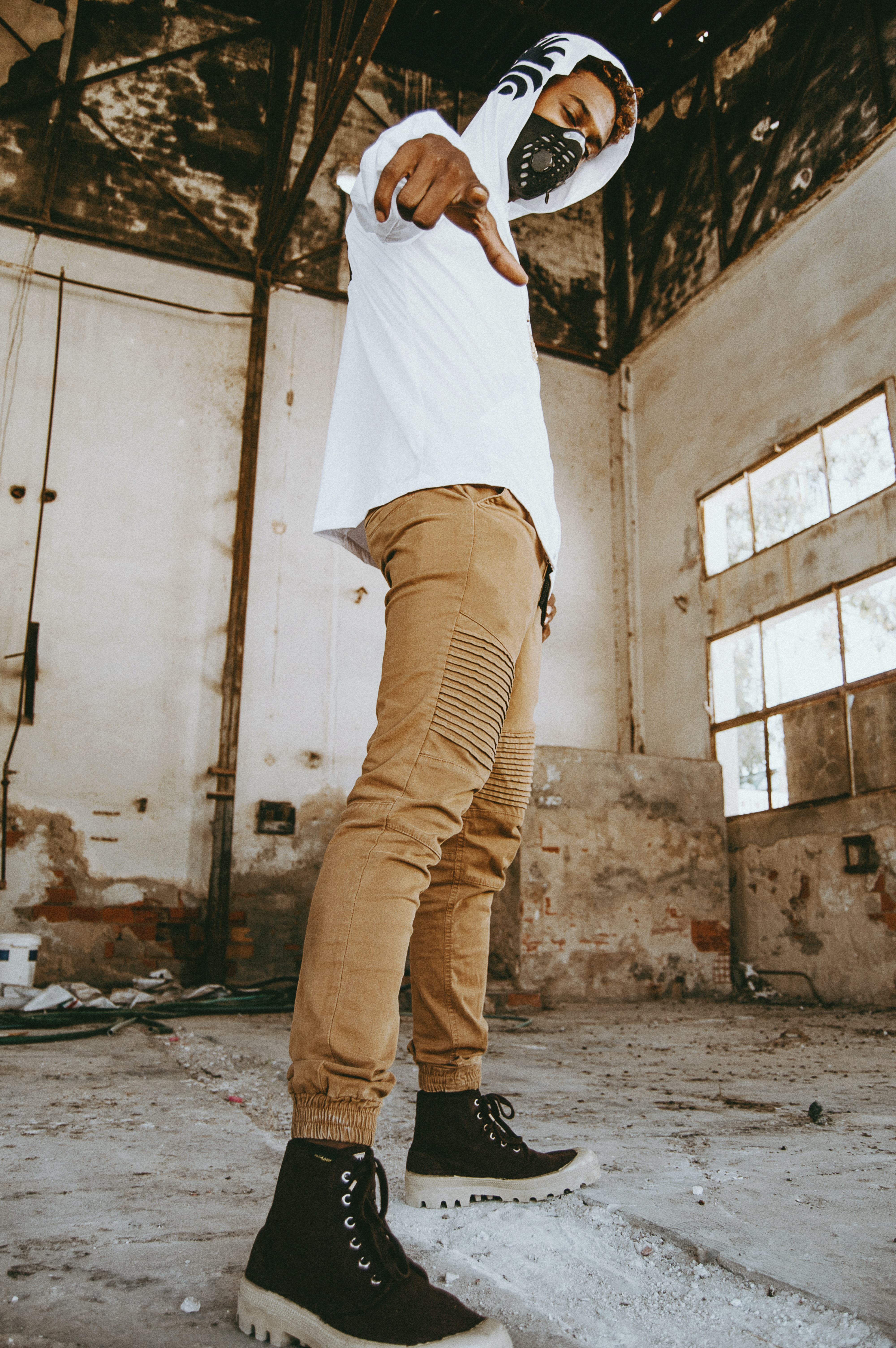 Man Wearing White Hoodie And Brown Skinny Jeans Standing Inside Abandoned Building Photo Free Image On Unsplash