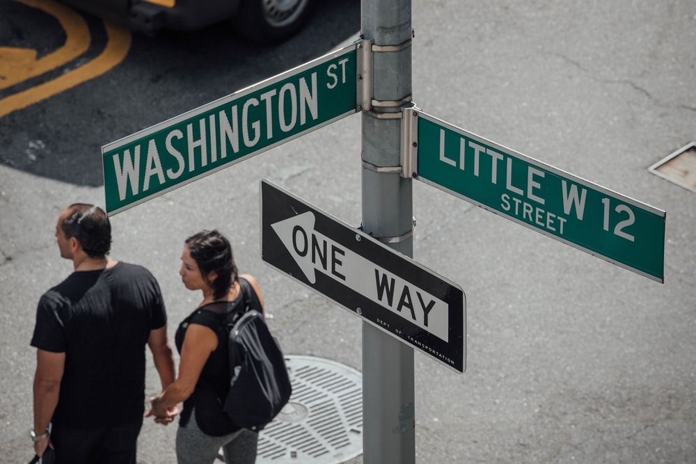 man and woman standing near street sign