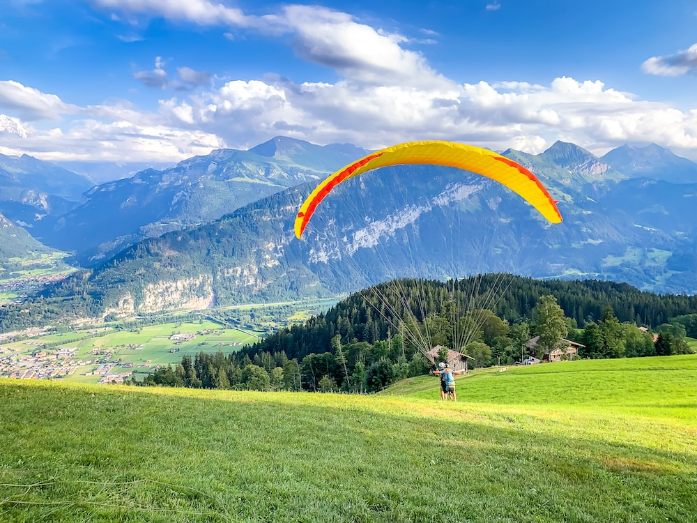 two men doing paragliding on the hill