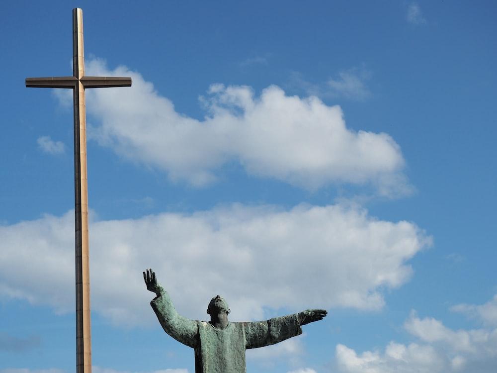 man statue beside cross