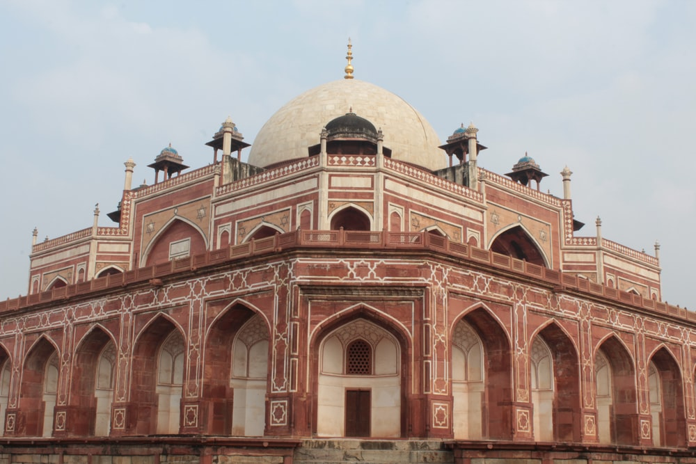 low-angle photography of red concrete dome top mosque