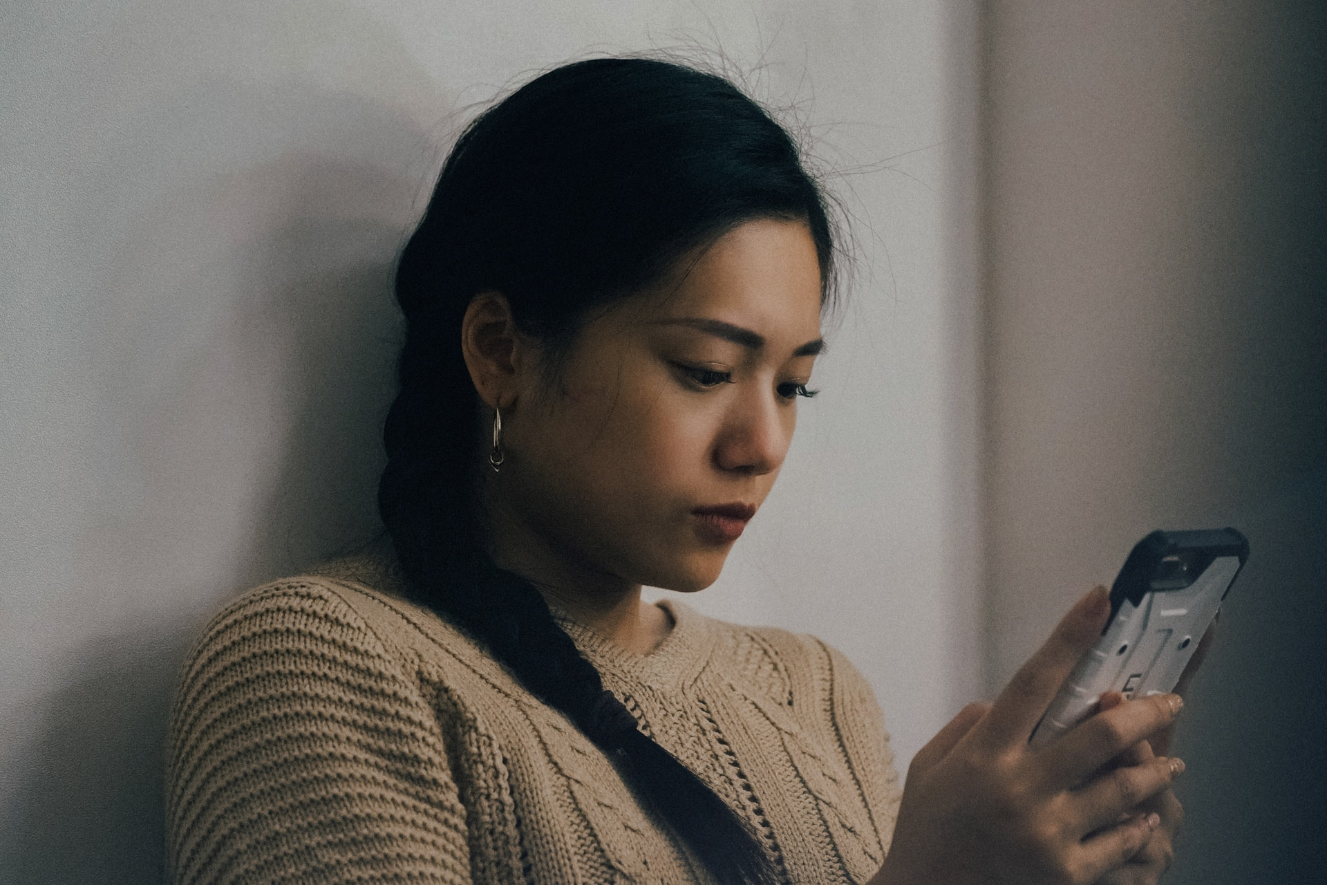 woman leaning back on white wall and using smartphone