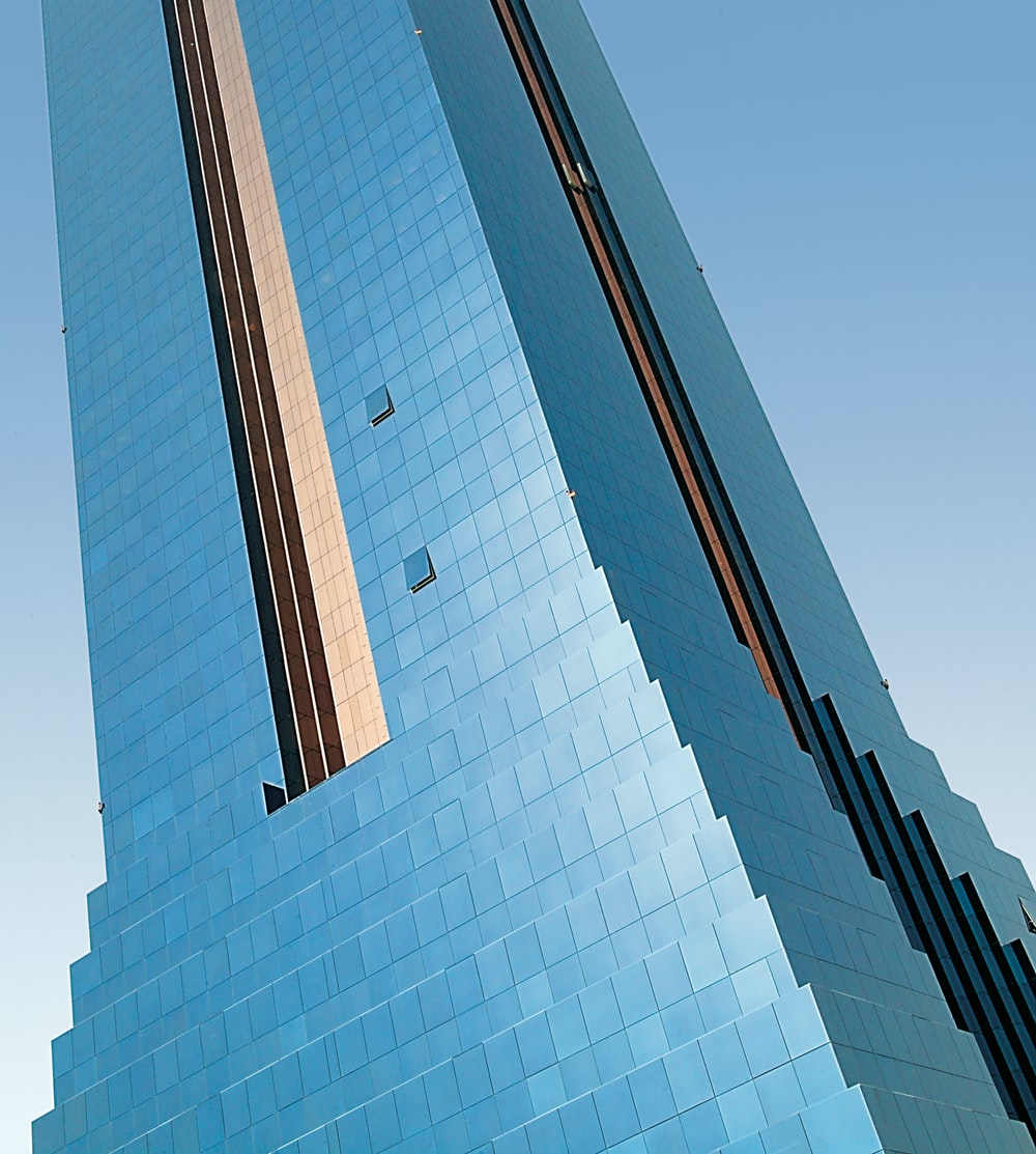 blue glass walled high-rise tower building