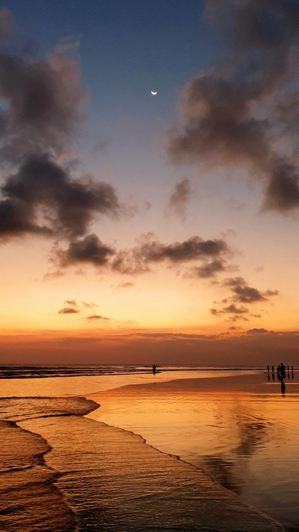 people near seashore under brown and orange skies