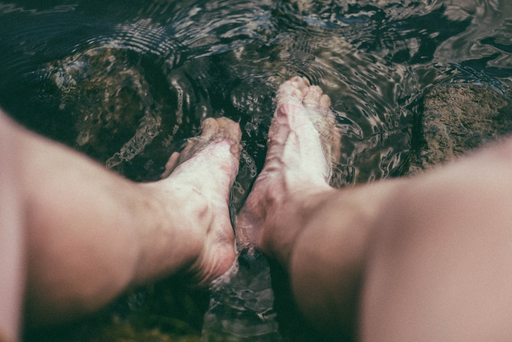 person's feet in water
