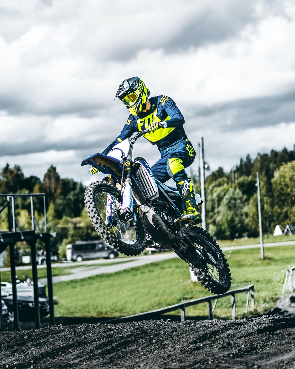 person wearing blue and yellow-green motocross suit midair