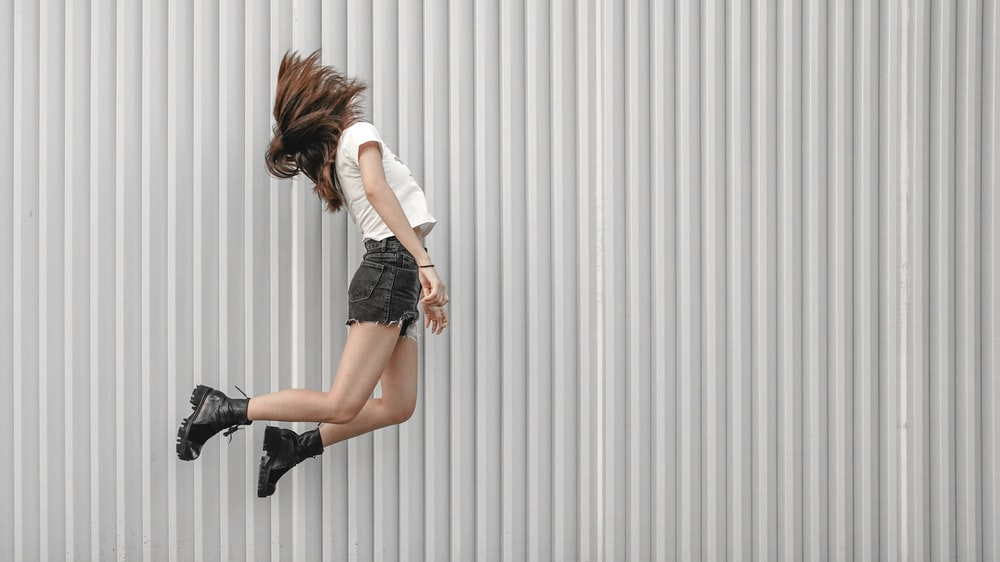 woman jumping beside wall