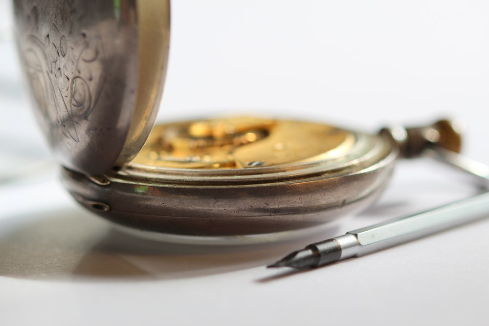 round gold-colored pocket watch beside pen