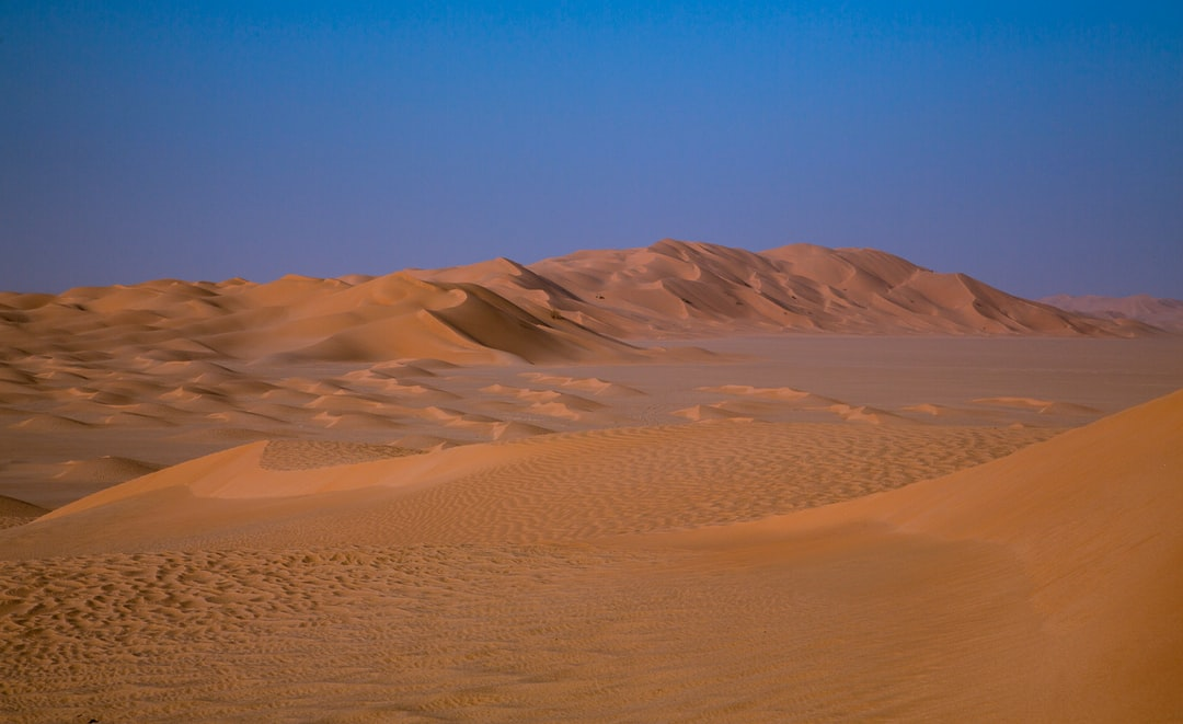 Sand dunes in brown and yellow colours under blue sky on a sunny day in Atlantis looking Rub al-Khali desert, Oman.