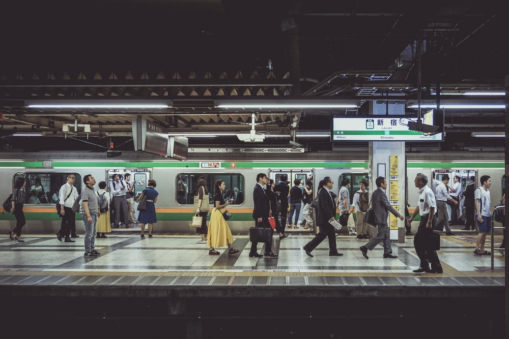 people standing and walking in train station