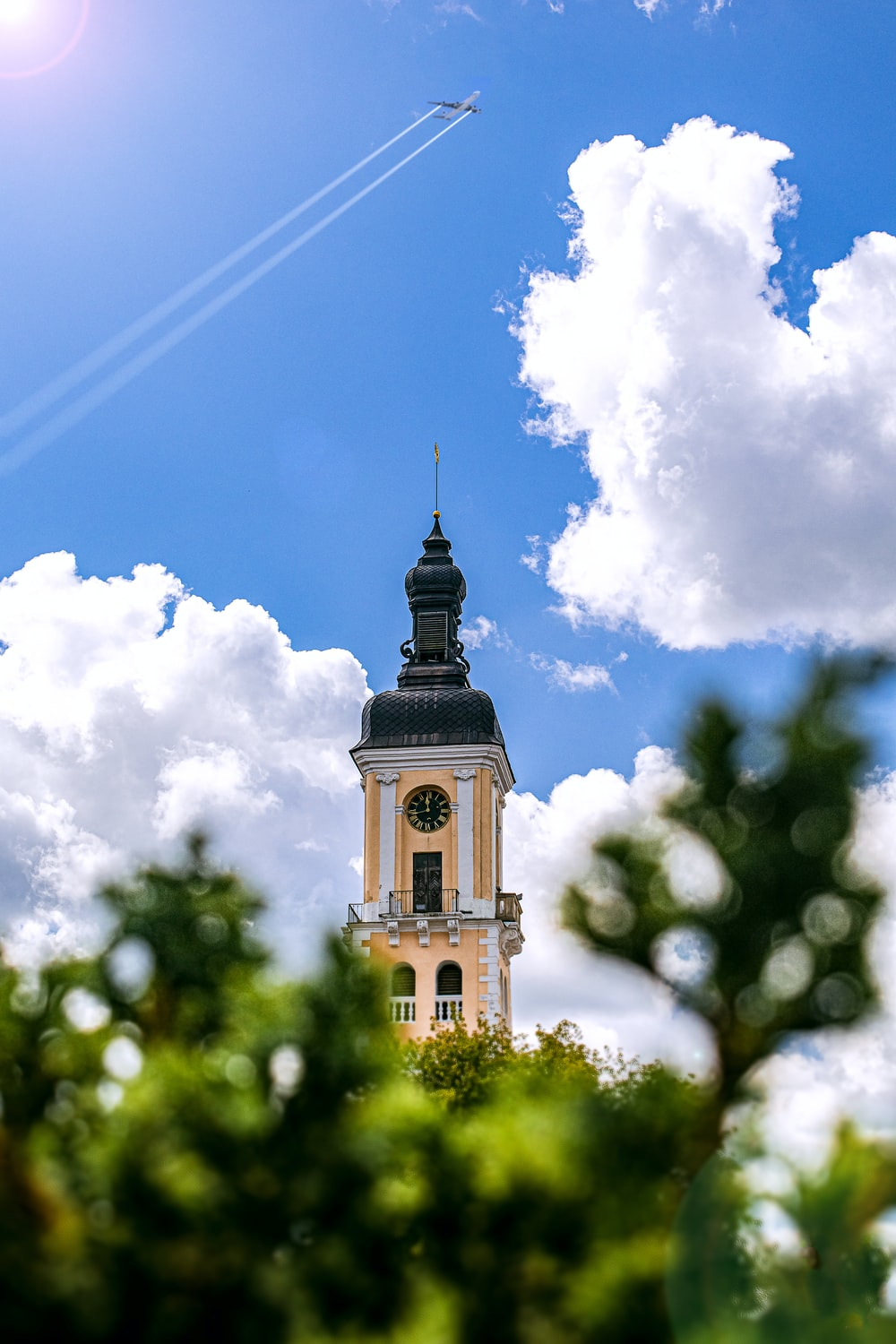 black and yellow church tower under a cloudy sky