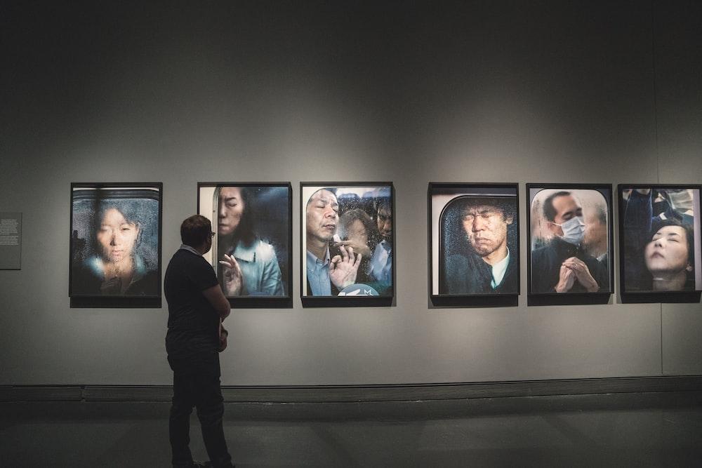 man looking at paintings on wall