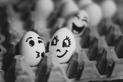 grayscale photography of two eggs on tray easter egg teams background