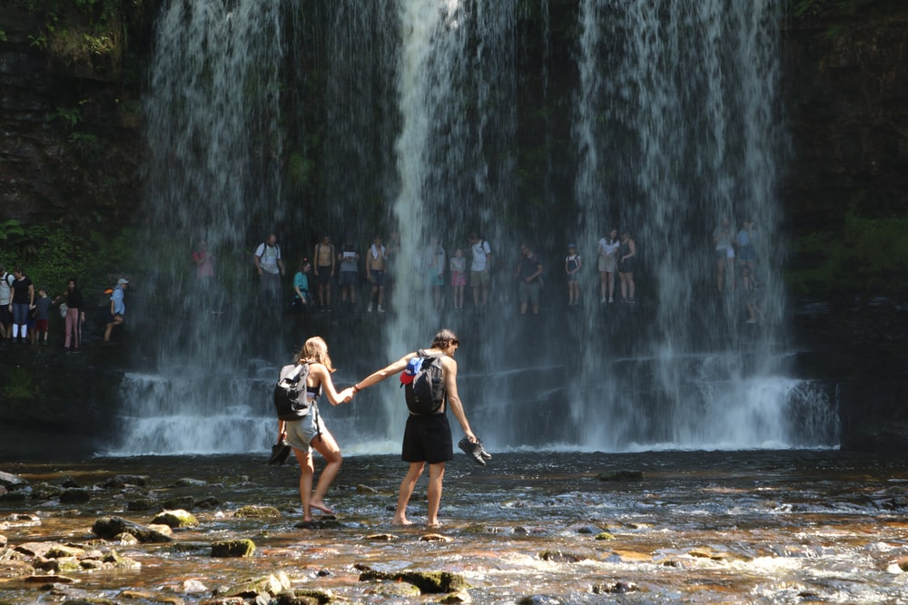 man and woman near waterfalls