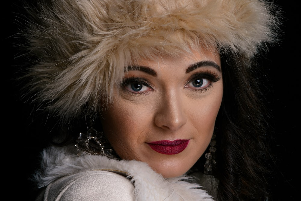 woman wearing white and brown fur coat smiling