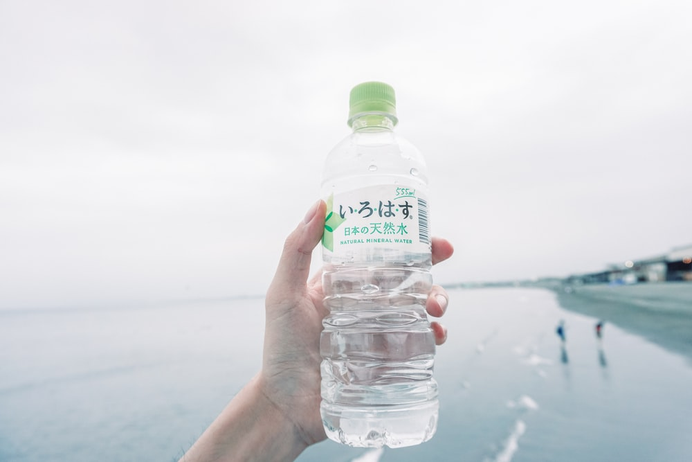 person holds plastic bottle