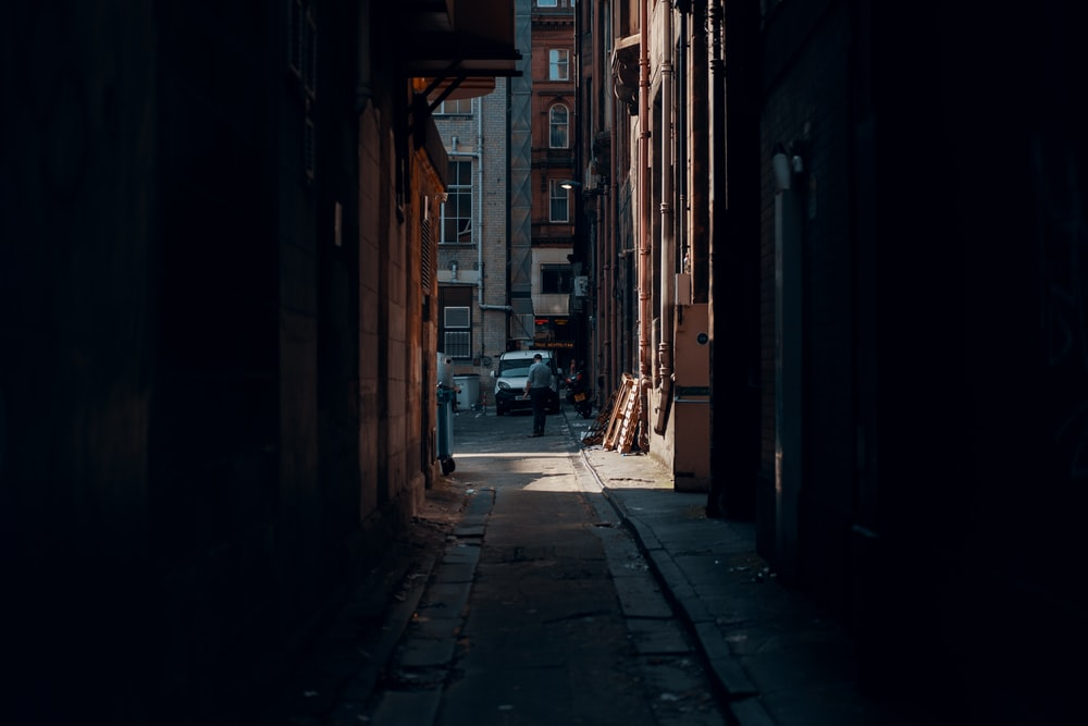 person walking beside building near vehicle