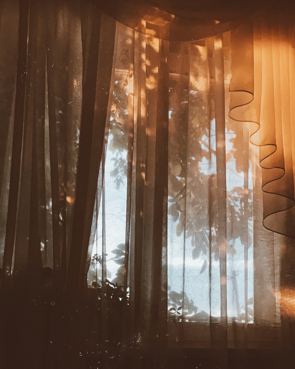 window with white curtain during day