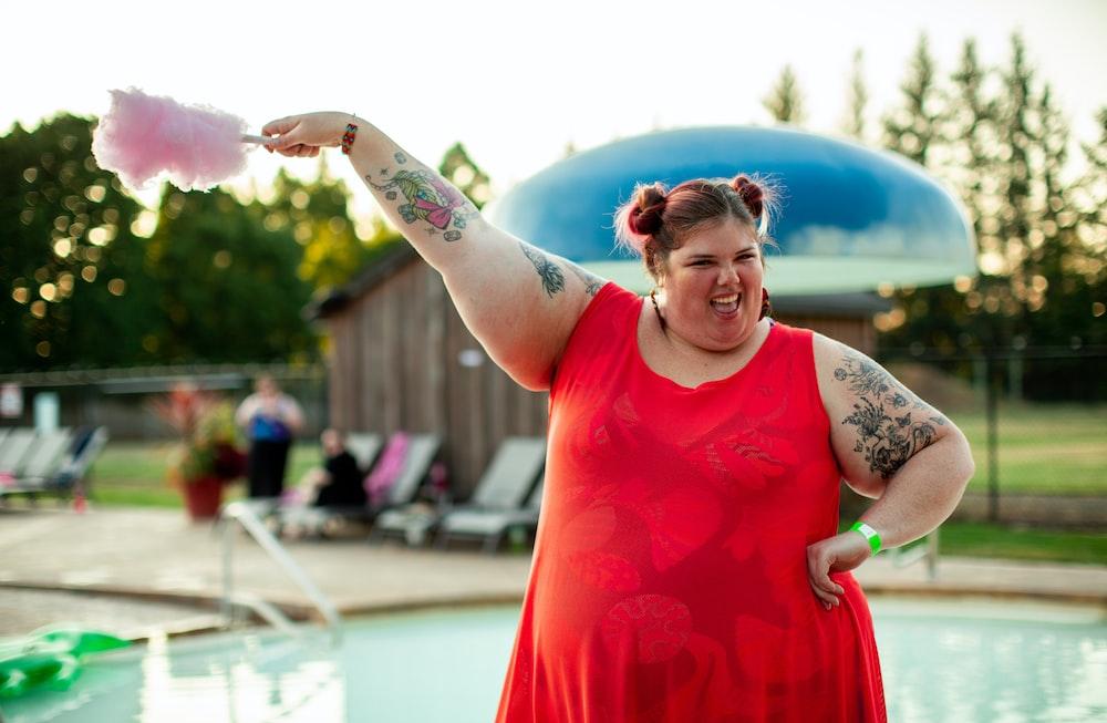 woman in red dress near pool