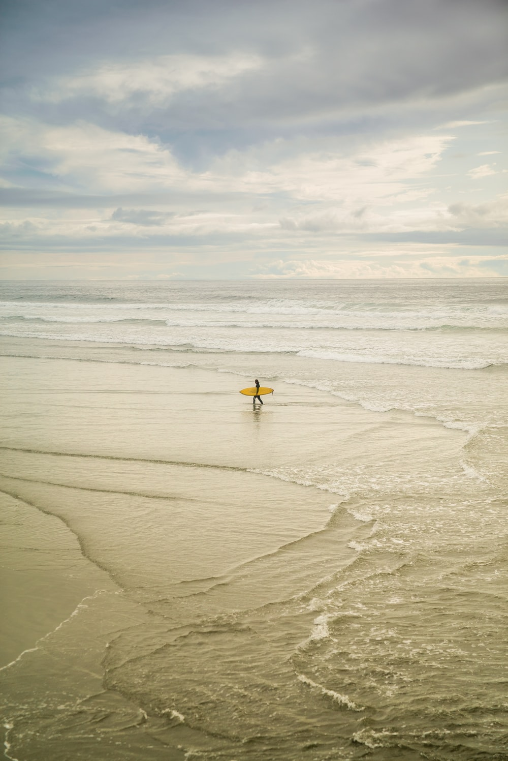 person holding yellow surfboard on seashore during daytime