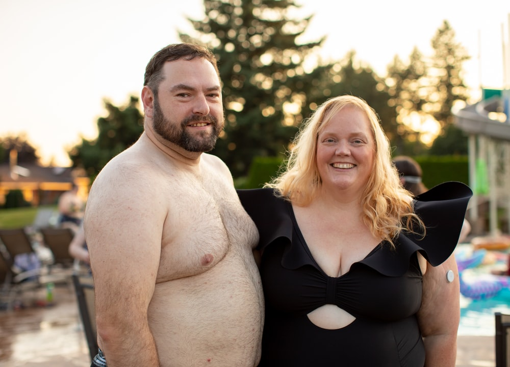 smiling topless man standing beside woman wearing black dress taking selfie
