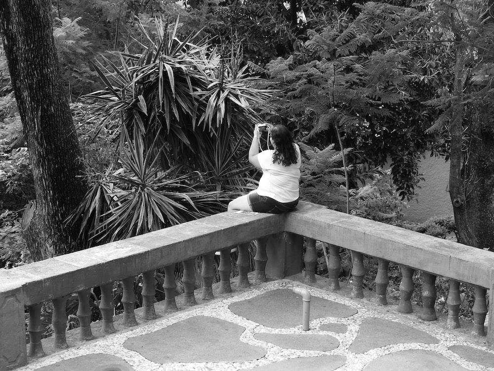 woman sitting on concrete handrail