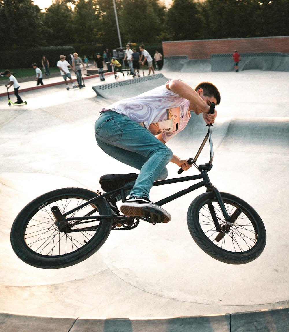 man wearing gray shirt riding BMX bicycle on air