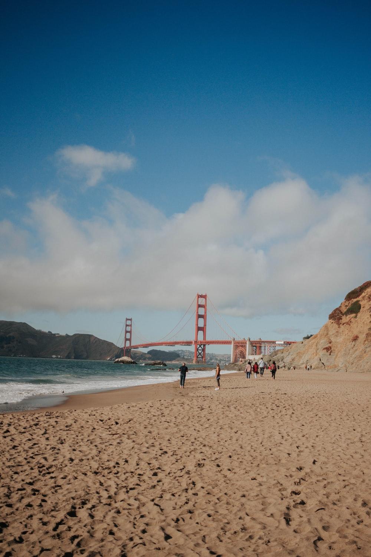 people walking on seashore near Golden Gate Bridge