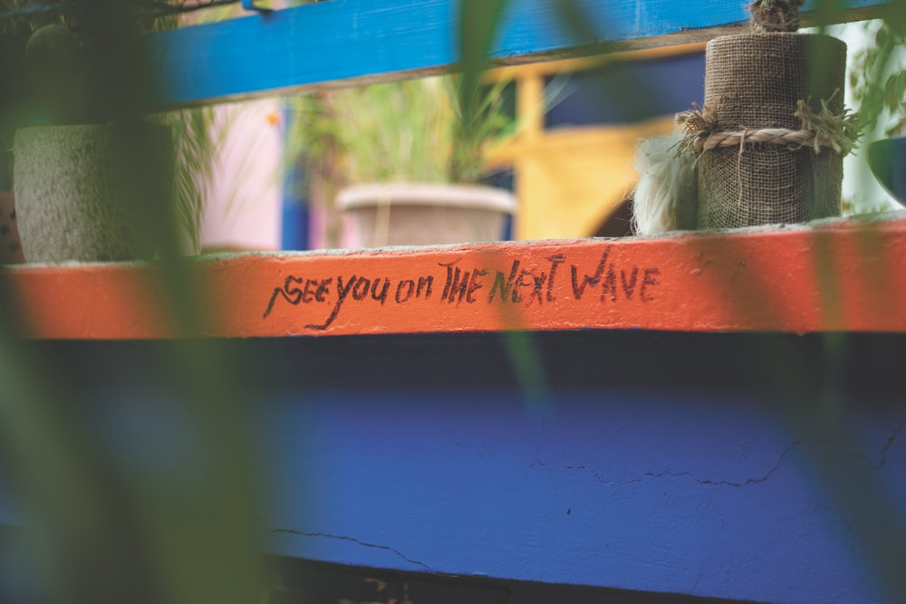see you on the next wave text handwritten on a wooden table
