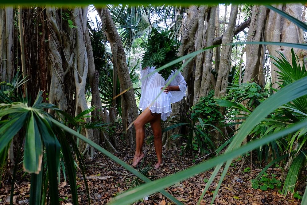 woman in white dress near trees