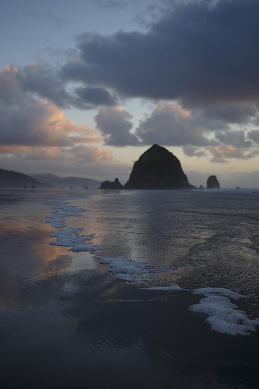 seashore near rocky mountain at daytime
