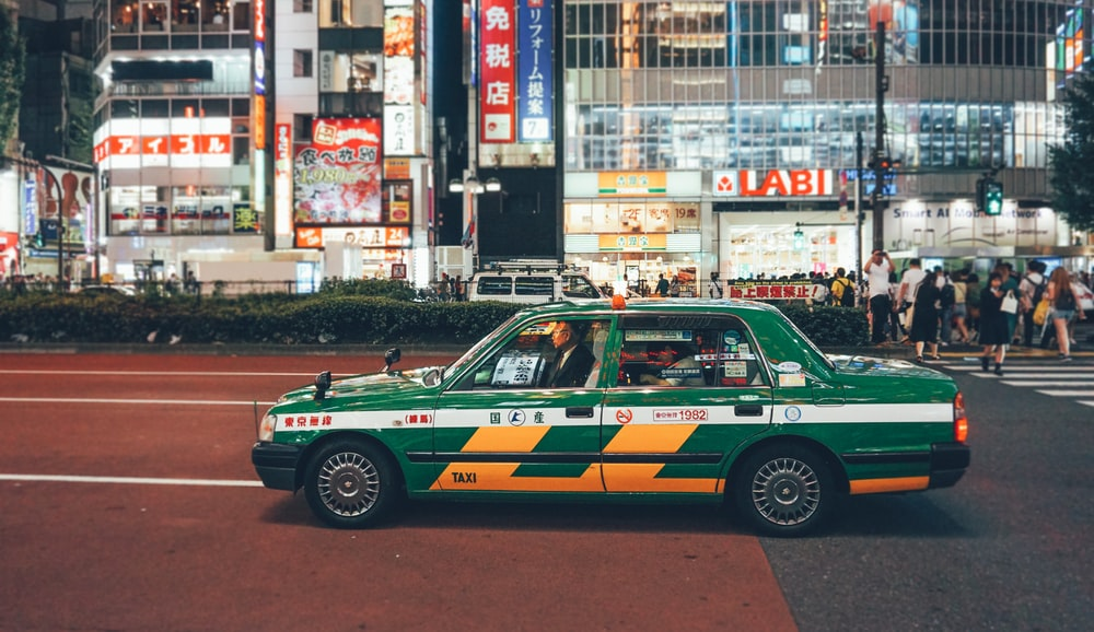 green taxi on road