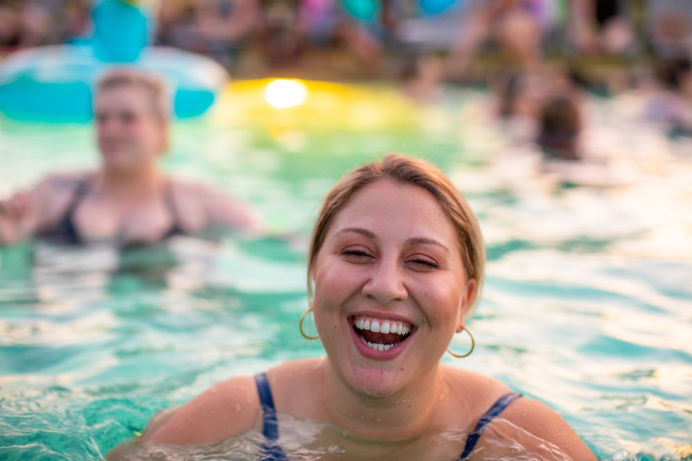 focus photography of woman swimming on pool
