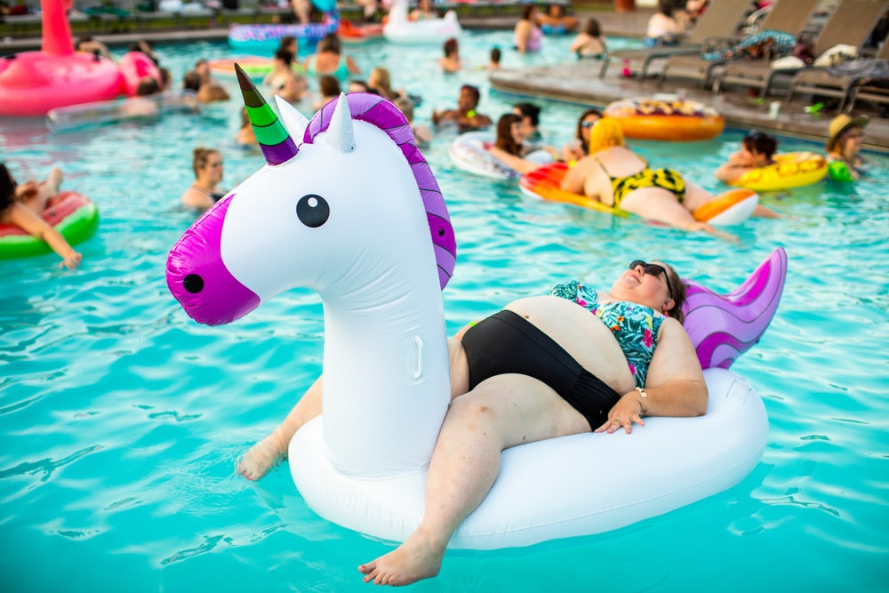 person lying on inflatable unicorn during daytime