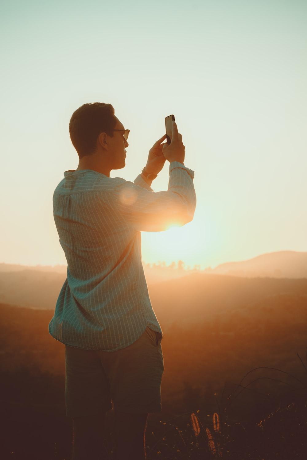man wearing green dress shirt taking picture during sunset