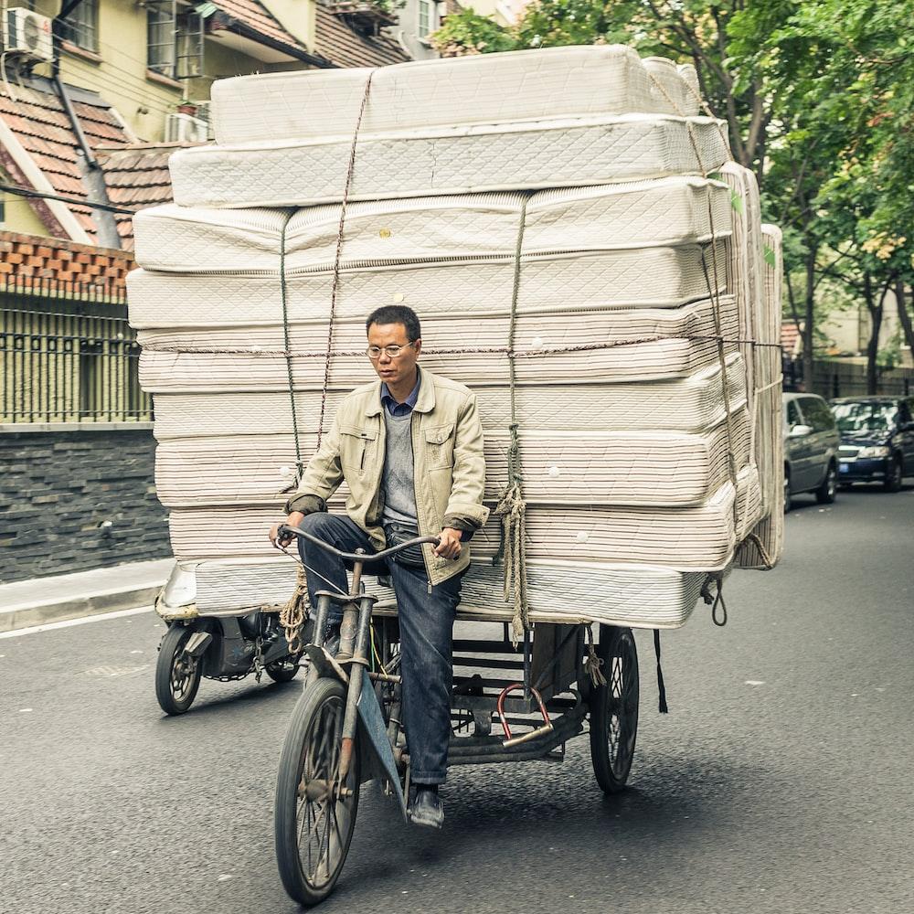man driving bicycle carrying mattress during daytime