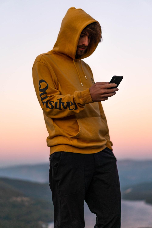 man wearing yellow hooded jacket