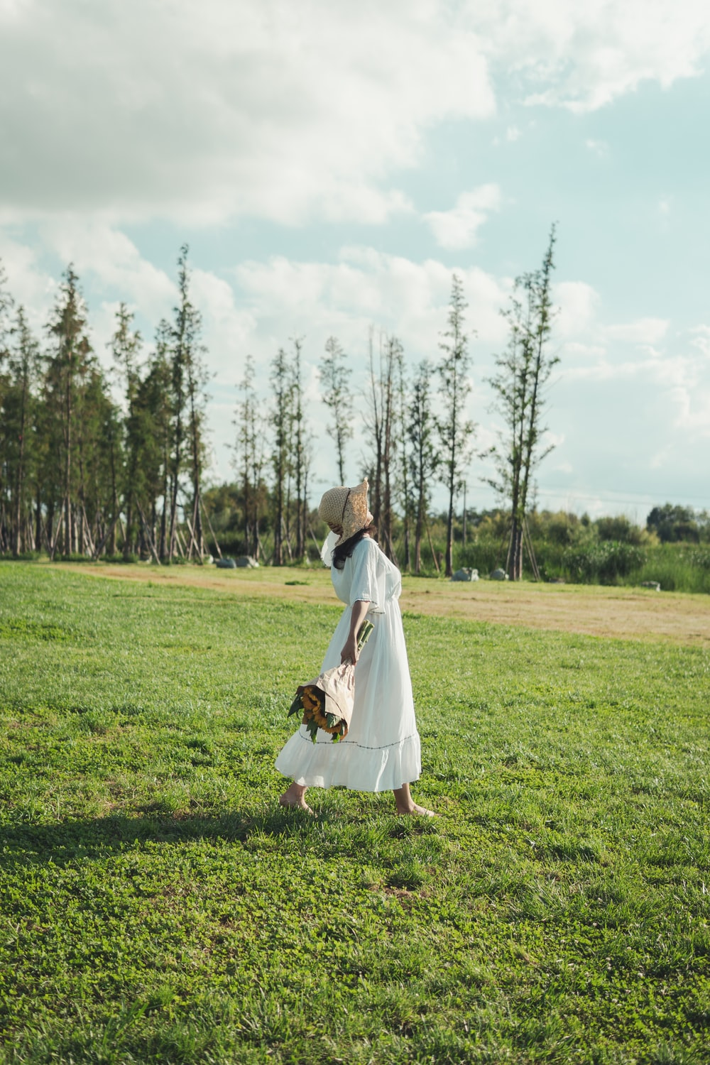 woman walking along a grass field