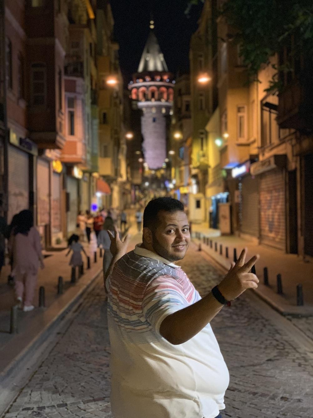 man walking in road between buildings
