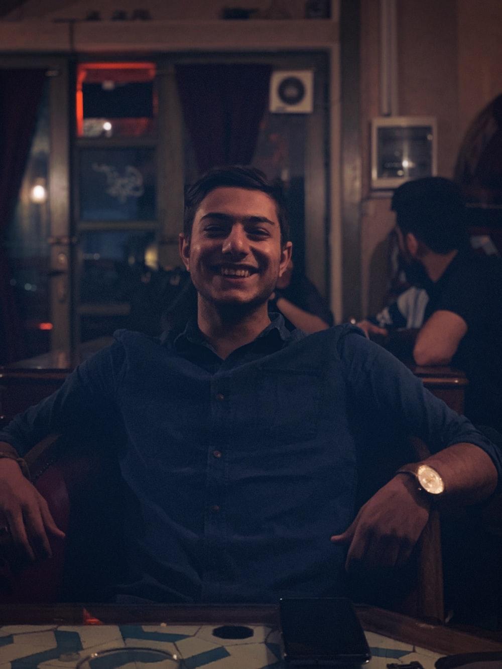 laughing man sitting beside table