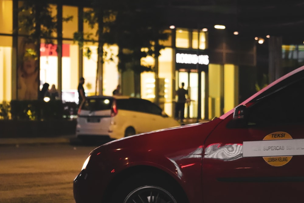 red car parked outside restaurant at night