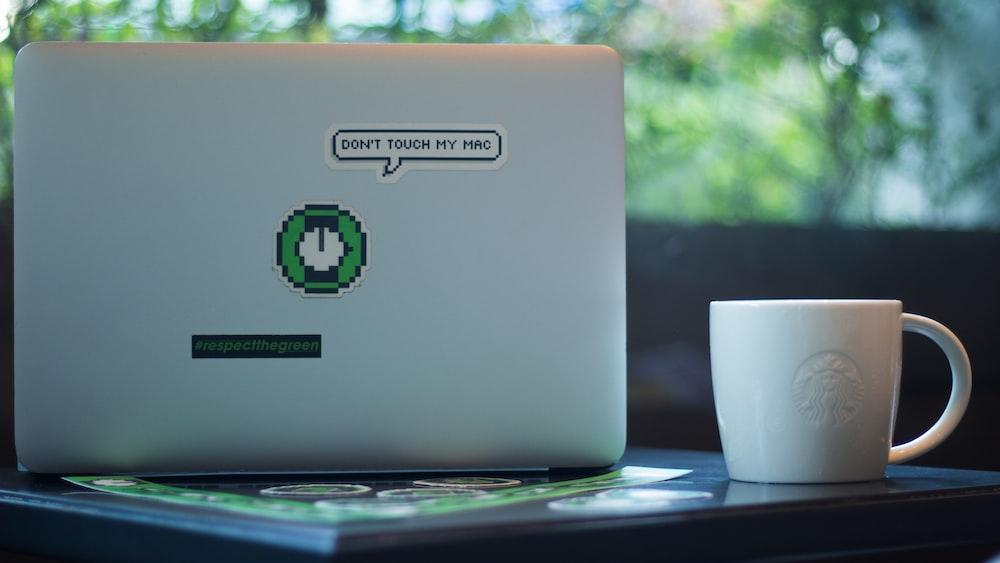 white mug beside laptop