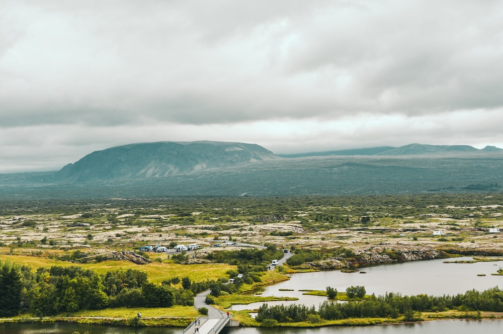 aerial photography of green land under cloudy sky