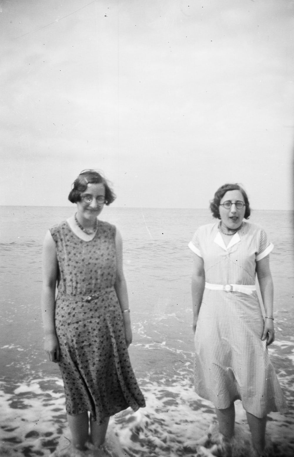 grayscale photography of two women standing in the sea