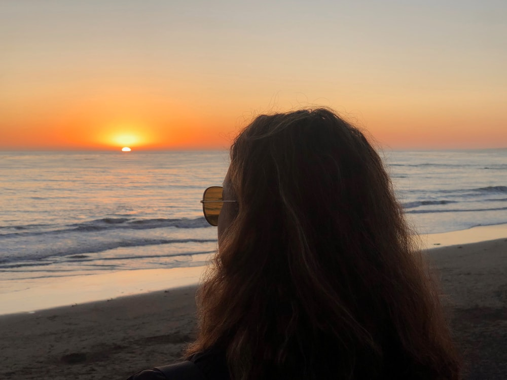 photo of woman wearing brown sunglass looking at sunset during sunset